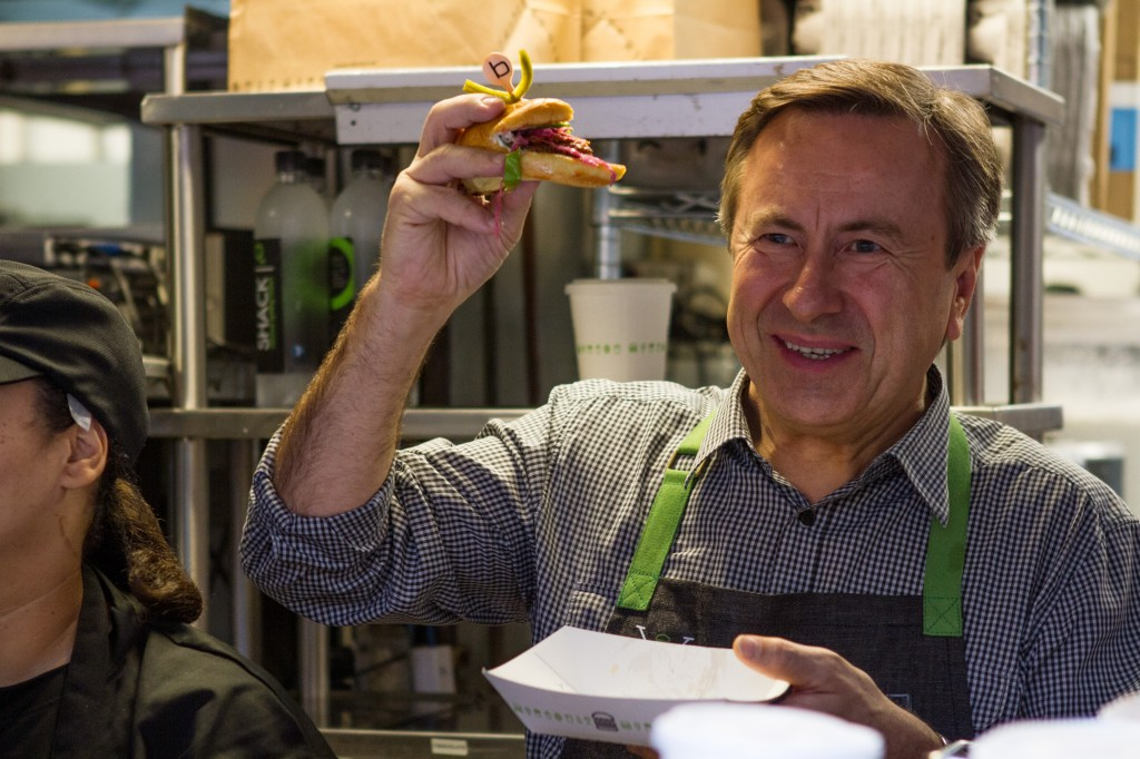 Daniel Boulud eats a burger at Shake Shack's Decade of Shack event.
