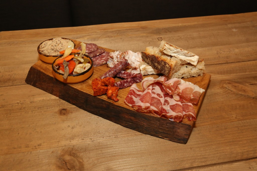 Black barn charcuterie plate with pickles and meat